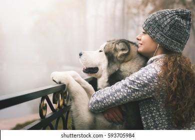 Imagem da jovem com seu cão, malamute do alasca, ao ar livre no outono ou inverno. Animal de estimação doméstico. Husky