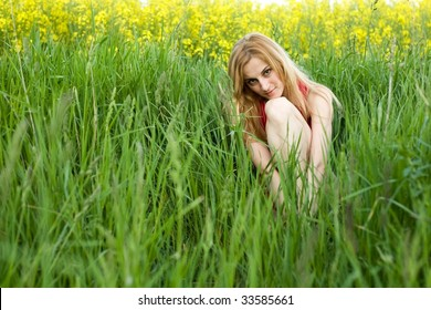 An image of young girl sitting in the grass