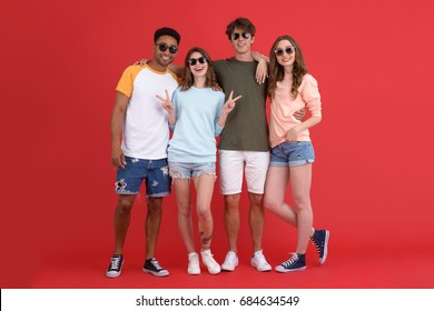 Image of young group of friends standing isolated over red background. Looking at camera.