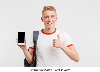 Image of young guy 16-18 years old wearing t-shirt and backpack showing thumb up while demonstrating smartphone isolated over white background