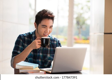 Image of a young guy drinking coffee while computing at a student cafe