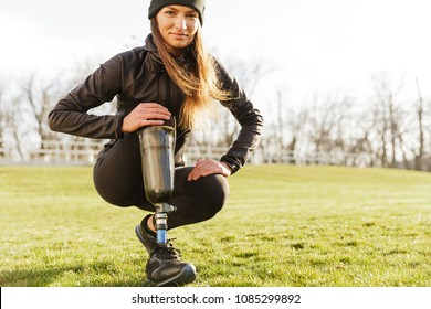 Image of young handicapped sportswoman in tracksuit squatting and touching bionic leg outside