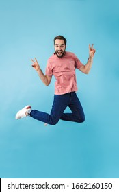Image of young handsome excited happy man jumping isolated over blue wall background make peace gesture.
