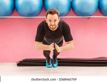 Image of a young handsome man clapping his hands while he is doing pushups in a gym.