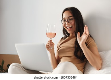 Image of young happy asian woman having video call, sitting on bed and drinking wine while waving hand at laptop and smiling.