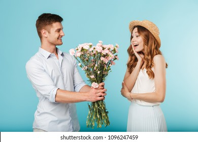 Image of young happy caucasian people man gives a flowers to his woman isolated over blue background.