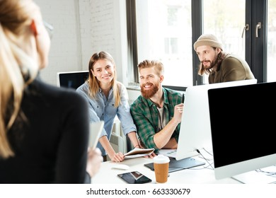 Image of young happy colleagues in office talking with each other using computer. Looking aside.