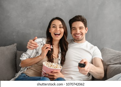 Image of young happy family sitting on sofa at home and looking at you showing remote control at camera and eating pop corn