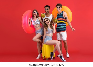 Image of young happy group of friends standing isolated over red background. Looking at camera holding cocktails and rubber rings.