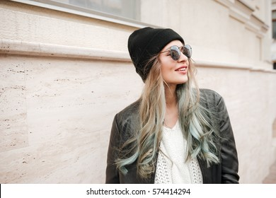 Image of young happy lady wearing hat and sunglasses walking on the street.