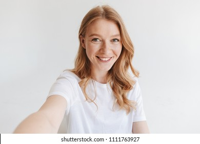 Image of young happy redhead woman isolated over white wall background make selfie looking camera.