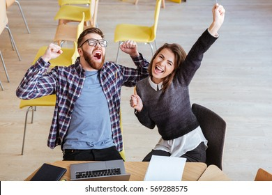 Image of young happy students sitting in library while make a winner gesture.