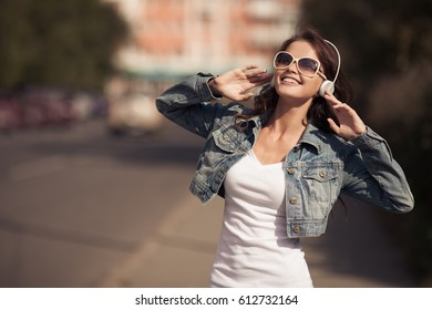 Image of young happy woman, listening music and having fun on the street. Lifestyle. Outdoor.