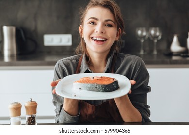 Image of young happy woman standing in kitchen while cooking fish. Looking at camera.
