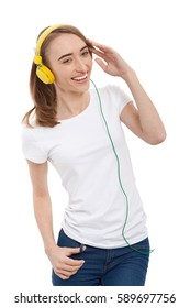 Image of young hipster girl wearing blank white t-shirt and blue jeans and listen to music in yellow headphones isolated on white.