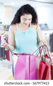 Image of young Indian woman looking into a shopping bag while standing in the fashion center