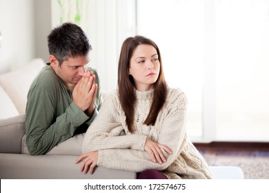 Image of young man begging his girlfriend to forgive him