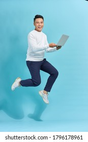 Image of young man dressed standing over blue background using laptop computer while jumping.