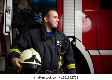 Image of young man firefighter with helmet in hand against background of fire truck