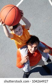 Image of young man and his son playing basketball