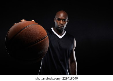 Image of young man holding a basketball against black background with copy space. Fit basketball player with focus on ball.