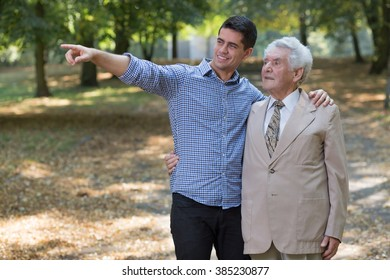 Image of young man showing something grandfather