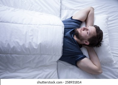 Image of young man sleeping after trying day