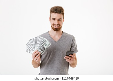 Image of young man standing isolated over white wall background using mobile phone holding money. Looking camera.