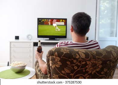 Image of a young man watching sports on TV