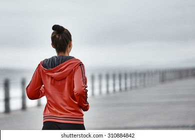 An image of a young mixed race females active life style as she takes her morning run along the sea side  while wearing a red jacket with lots of copy space