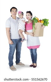 Image of a young mother holding vegetable on paper bag while standing on studio with her husband and daughter