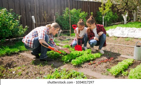 Image of young mother with two girls working in garden