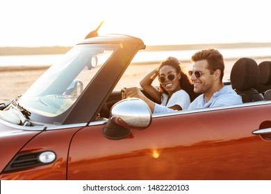 Image of young multiethnic couple man and woman smiling while driving convertible stylish car by seaside