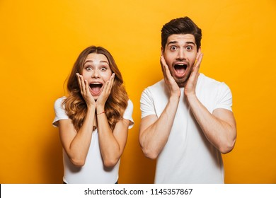 Image of young people man and woman in basic clothing screaming in surprise or delight and touching cheeks isolated over yellow background