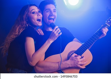 Image of young positive optimistic loving couple musicians group duet on scene in night club over dark background with flash lights.