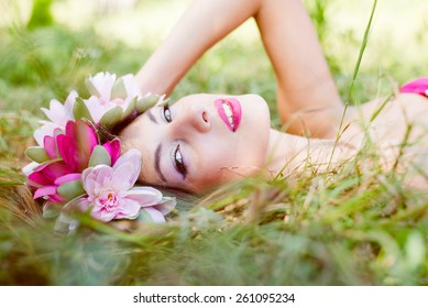 Image of young pretty lady fairy princess with flowers crown relaxing laying on summer green grass