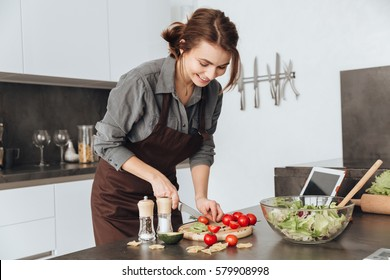 Image of young pretty woman standing in kitchen using tablet computer and cooking with the tomatoes and avocado.