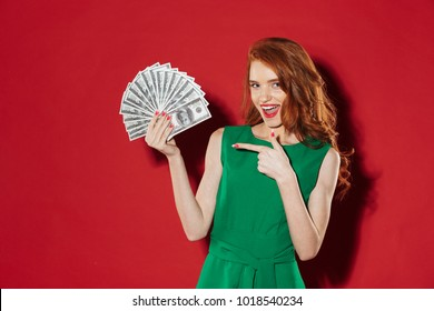 Image of young redhead girl in green dress posing over red wall background with money. Looking camera pointing.