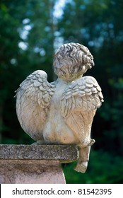 Image of an / young and sad Angel / sitting on a pillar in front of a forest