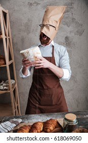 Image of young screaming man baker standing with paper bag on head wearing glasses at bakery holding bread.
