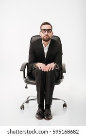 Image of young serious businessman over white background sitting on chair.