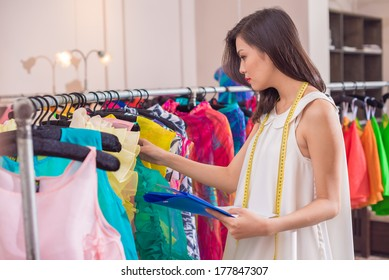 Image of a young shop owner accounting income clothes on the foreground