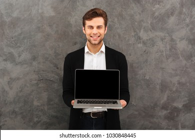 Image of young smiling businessman standing over grey wall background. Looking camera showing display of laptop computer.