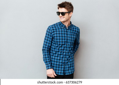 Image of young smiling man wearing sunglasses standing over grey wall and looking aside.