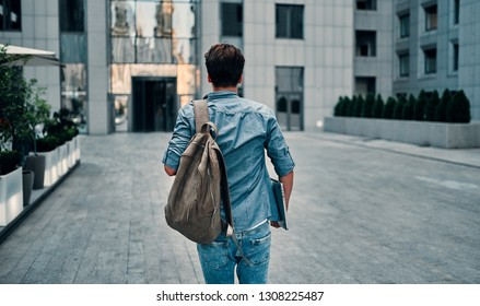 Image of young student in headphones with backpack walking in the city holding laptop computer.