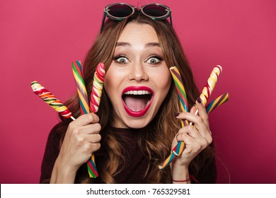 Image of young surprised funny lady wearing glasses standing isolated over pink background. Looking camera eating candy.