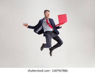 Image of young surprised man over white studio using laptop computer while jumping. illumination in motion
