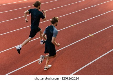 Image of young two twins sportsmen brothers running at the stadium outdoors.