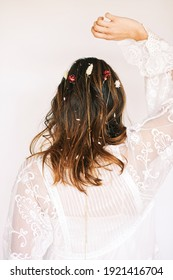 Image of young woman with boho hairstyle, back view. Hair with flowers and chains