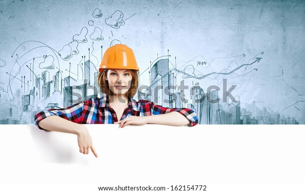 Image of young woman builder wearing helmet and holding blank banner